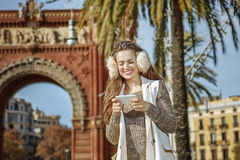 Happy elegant woman in Barcelona, Spain writing sms Royalty Free Stock Photo