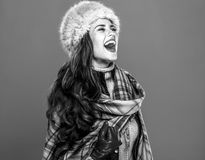 Happy elegant woman in fur hat isolated on cold blue rejoicing. Winter things. Portrait of happy elegant woman in fur hat isolated on cold blue rejoicing Royalty Free Stock Images