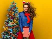 Happy elegant woman near Christmas tree with a book jumping Royalty Free Stock Photography