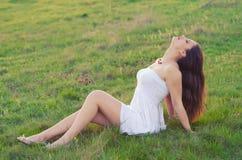 Happy elegant woman sitting on the spring meadow Stock Photos