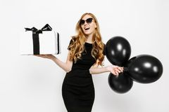 Happy elegant young girl in black dress happily holding gift with black Friday ribbon and black balloons on white background