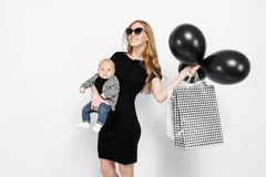 Happy elegant young mom, girl in black dress happily holding bags with black balloons, and little baby on white background. Baby