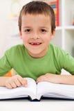 Happy elementary school boy practice reading. Happy smiling elementary school boy with missing tooth practice reading Stock Photo