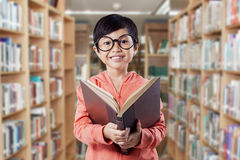 Happy elementary school student reads book Royalty Free Stock Image