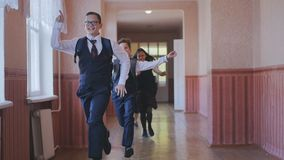Happy students run out of the classroom and run down the hall stock footage