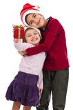 Happy embraced children with present at Christmas Stock Photos
