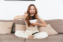 Happy emotional amazing pretty lady watch TV. Picture of young happy emotional amazing pretty lady sitting on sofa indoors. Looking camera eating corn flakes Stock Photography