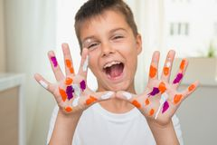 Happy emotional boy with painted hands show them at camera, joyful artist. Education and creativity theme. stock photography