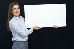 Happy emotional business woman holding white sign board studio p. Ortrait. Black isolated Stock Images