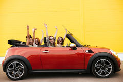 Happy emotional four young women friends sitting in car Stock Photo