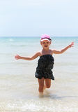 Happy emotional kid girl running in the blue sea in dress and en Stock Photo