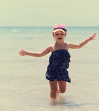 Happy emotional kid girl running in the blue sea in dress and en Royalty Free Stock Images