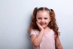 Happy emotional kid girl smiling with hand at face Royalty Free Stock Images