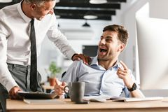 Happy emotional men colleagues in office working with computer. Picture of excited happy emotional men colleagues in office working with computer royalty free stock image