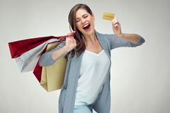 Happy emotional woman holding credit card and shopping bag. Stock Photos