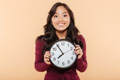 Happy emotions of asian woman with curly long hair holding clock. Showing nearly 8, waiting for something pleasant over peach background Stock Photos