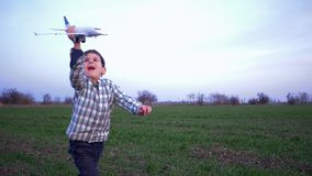 Happy emotions of child, boy runs with airplane in hands on background of green field and blue sky. Happy emotions of the child, boy runs with airplane in hands stock footage