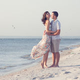 Happy emotive adult couple. On the sea shore. copy space. White sand, blue water, seagulls stock images