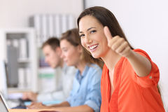 Happy employee looking at you with thumbs up. Portrait of a happy employee looking at you with thumbs up sitting in a desktop at office Stock Images