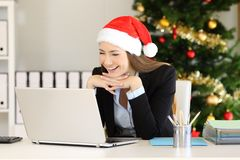 Happy employee reading on line at office in christmas royalty free stock photography