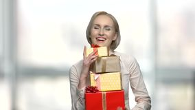 Happy employee received a surprise bonus or gift. Smiling pretty woman holding pile of gift-wrapped boxes. Presents from beloved man stock video footage