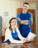 Happy  employee in uniform with financial documents at table in Royalty Free Stock Photos