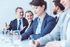 Happy employees during company meeting. Happy employees in elegant suits talking during company meeting Royalty Free Stock Photos