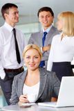 Happy employer. Pretty businesswoman looking at camera at workplace with several partners on background Royalty Free Stock Image