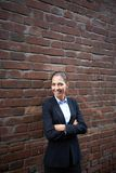 Happy employer. Image of happy businesswoman standing by brick wall and looking at camera Stock Photo