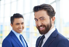 Happy employer. Image of smiling businessman in formalwear looking at camera on background of his colleague Stock Image