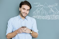 Happy employer smiling while dreaming about seeing the mountains. Pleasant thoughts. Cheerful handsome employer smiling while standing with a modern smartphone Royalty Free Stock Image