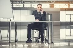 Happy employer speaking by phone. Full length portrait of cheerful young businessman talking by mobile while working at desk. Glad worker during labor concept Stock Photo