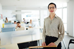 Happy employer. Successful employer looking at camera on background of working managers royalty free stock photography
