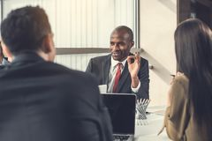 Happy employer talking with colleagues. Outgoing businessman telling with affiliates while locating at desk. Cheerful workers during job concept Stock Photos