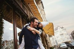 Happy enamored couple is standing outdoors near the decorated shop windows, hugging and kissing each other. Happy enamored couple is walking and having fun stock image
