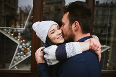 Happy enamored couple is standing outdoors near the decorated shop windows, hugging and kissing each other. Valentines day concept royalty free stock images
