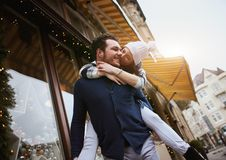 Happy enamored couple is standing outdoors near the decorated shop windows, hugging and kissing each other. Happy enamored couple is walking and having fun stock photos