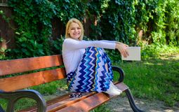 Happy ending makes her delighted. Lady pretty happy hold book garden sunny day. Girl sit bench relaxing with book, green. Nature background. Reading can help royalty free stock photography