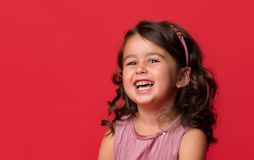 Happy energetic little girl. On red pointing fresh. Candid portrait of cheering beautiful young white Caucasian woman on red background Royalty Free Stock Photography