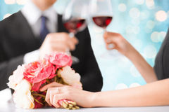 Happy engaged couple with flowers and wine glasses Stock Images