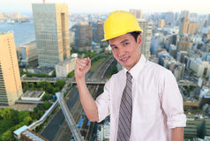 Happy engineer with arm raised, concept of successful, city back Royalty Free Stock Images