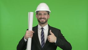Happy Engineer with Blueprint showing Thumbs Up against Chroma Key. The Happy Engineer with Blueprint showing Thumbs Up against Chroma Key stock video footage