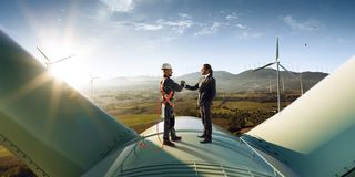 Happy engineer and businessman shake hands after good work. They standing a top of windmill. Around wind generators. And beautiful sunset landscape royalty free stock images