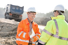 Happy engineer discussing with colleague at construction site on sunny day Stock Image