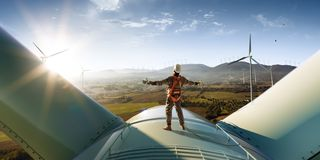 Happy engineer feel success after good work. He standing a top of windmill and looking beautiful sunset. Landscape stock photos