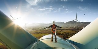 Happy engineer feel success after good work. He standing a top of windmill and looking beautiful sunset. Landscape royalty free stock image