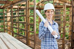 Happy Engineer Holding Blueprint In Wooden Cabin royalty free stock images