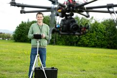 Happy Engineer Operating UAV in Park. UAV helicopter flying while happy young engineer operating it in background at park Stock Photography