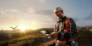 Happy engineer planning new project. He standing a top mount and looking in tablet. Around beautiful landscape royalty free stock image