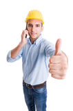 Happy engineer showing ok while talking on smartphone Stock Photography